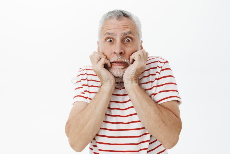 Retrato del hombre mayor carismático ansioso y asustado intenso con la barba gris y del pelo que lleva a cabo las manos cerca de  imagen de archivo
