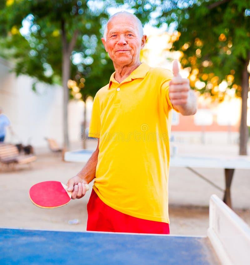 Retrato del hombre mayor con las estafas para los tenis de mesa que muestran el th foto de archivo