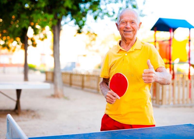 Retrato del hombre mayor con las estafas para los tenis de mesa que muestran el th fotos de archivo libres de regalías