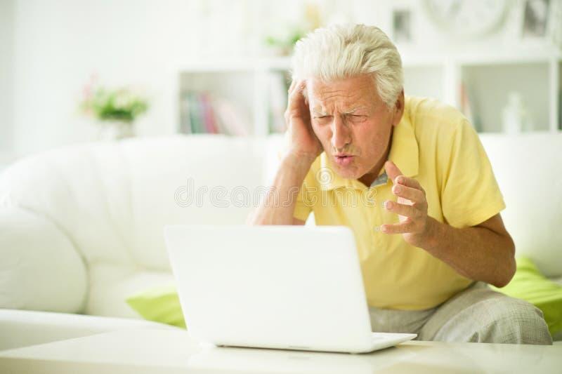 Retrato del hombre mayor emocional usando el ordenador port?til fotos de archivo libres de regalías