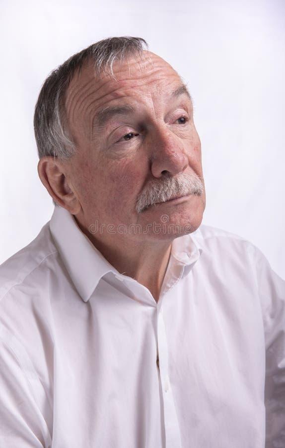 Retrato del hombre mayor en el fondo blanco fotografía de archivo