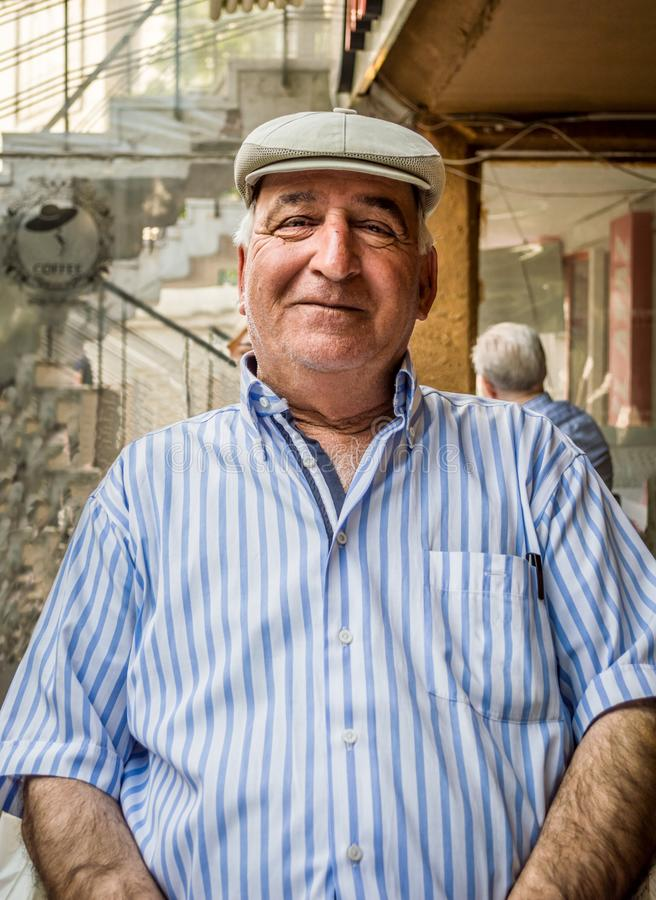 Retrato del hombre mayor feliz que lleva la camisa rayada azul y el casquillo plano imagen de archivo libre de regalías