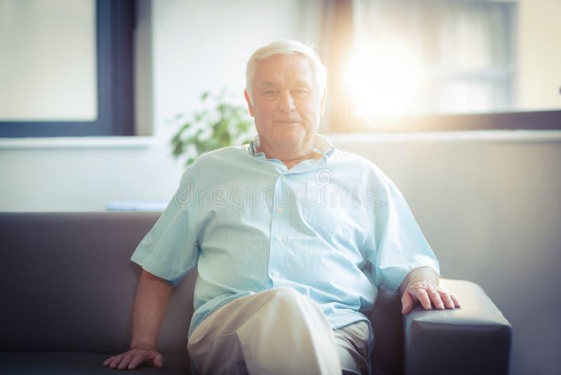 Retrato del hombre mayor feliz que se sienta en el sofá imagen de archivo libre de regalías
