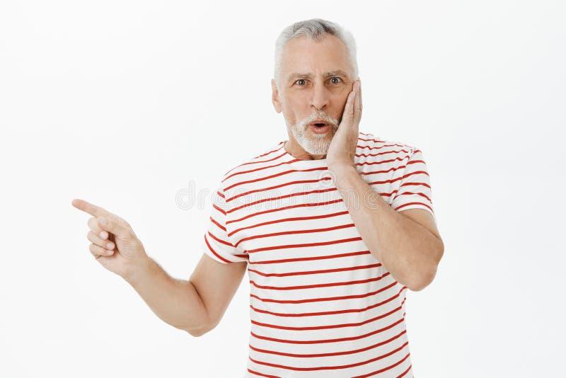 Retrato del hombre mayor impresionado encantador sorprendido y chocado con la barba y el pelo gris que presionan la mano a la mej imágenes de archivo libres de regalías