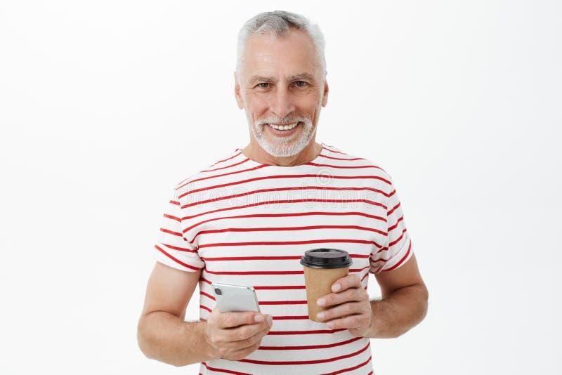 Retrato del hombre mayor moderno encantador que vive vida activa usando el smartphone para la comunicación que sostiene la taza d fotografía de archivo
