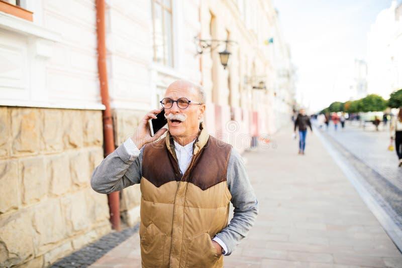 Retrato del hombre mayor moderno que usa smartphone al aire libre, en calle de la ciudad foto de archivo libre de regalías