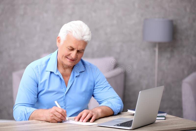 Retrato del hombre mayor que completa el boleto de lotería imagenes de archivo