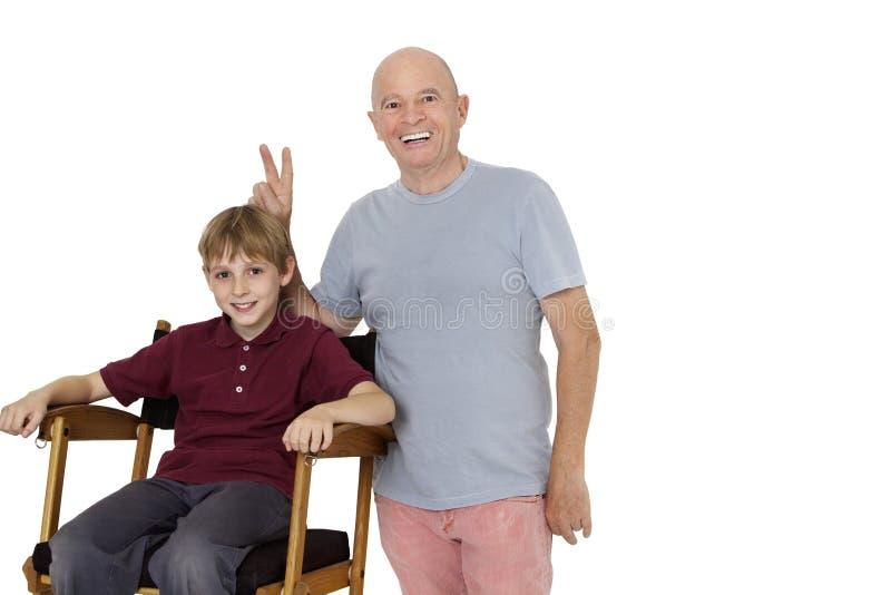 Retrato del hombre mayor que gesticula el signo de la paz mientras que muchacho pre-adolescente que se sienta en la silla del dire imágenes de archivo libres de regalías