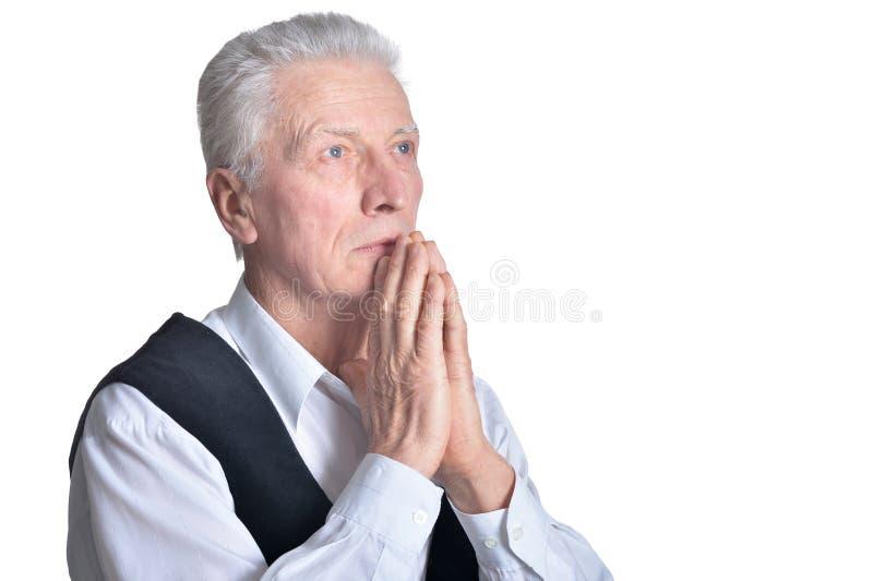 Retrato del hombre mayor que ruega en el fondo blanco fotografía de archivo