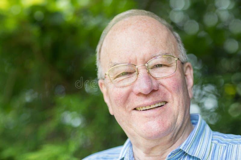 Retrato del hombre mayor que se relaja en jardín foto de archivo