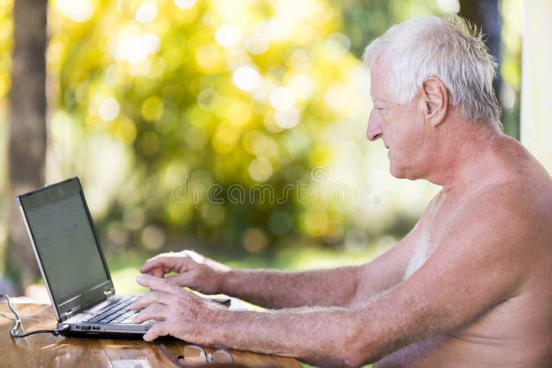 Retrato del hombre mayor que trabaja con el ordenador portátil en al aire libre sin la camisa imagen de archivo libre de regalías