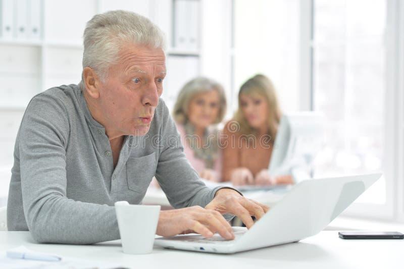 Retrato del hombre mayor que trabaja con el ordenador port?til en la oficina moderna foto de archivo