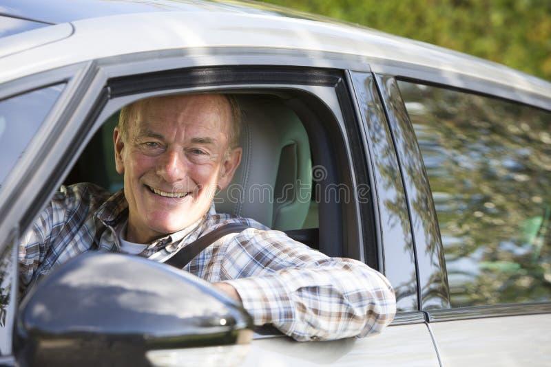 Retrato del hombre mayor sonriente que conduce el coche foto de archivo