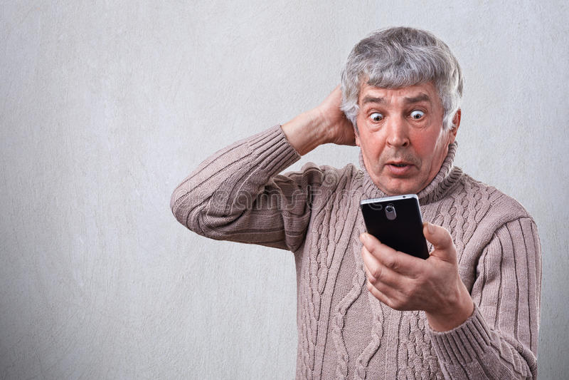 Retrato del hombre mayor sorprendido que mira con los ojos abiertos de par en par en su smartphone que son chocados por lo que él fotografía de archivo