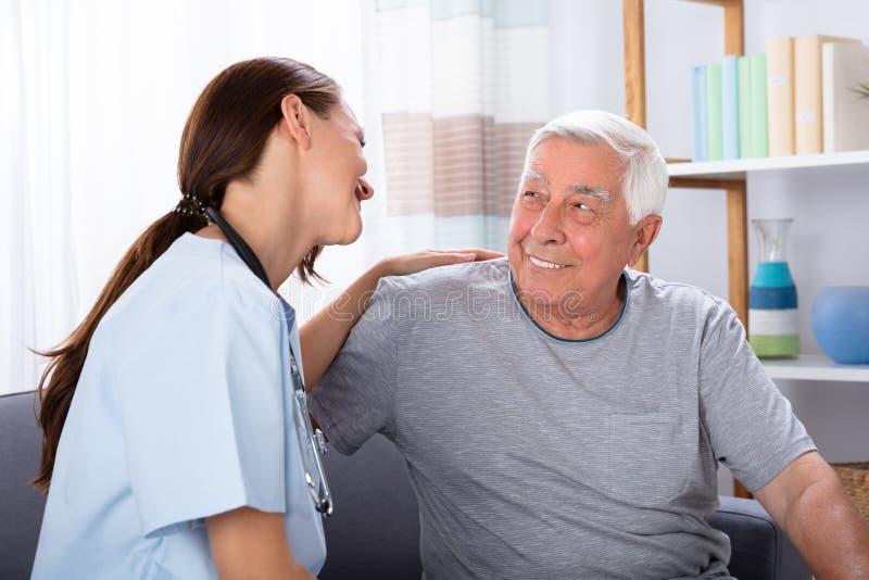 Retrato del hombre mayor y de la enfermera felices imagen de archivo libre de regalías