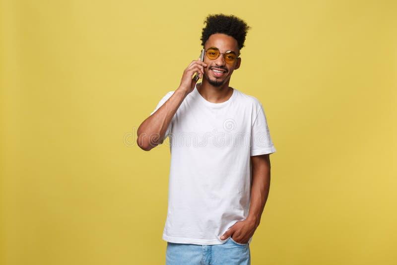 Retrato del hombre negro joven fresco que habla en el teléfono móvil Aislado en fondo amarillo fotos de archivo libres de regalías