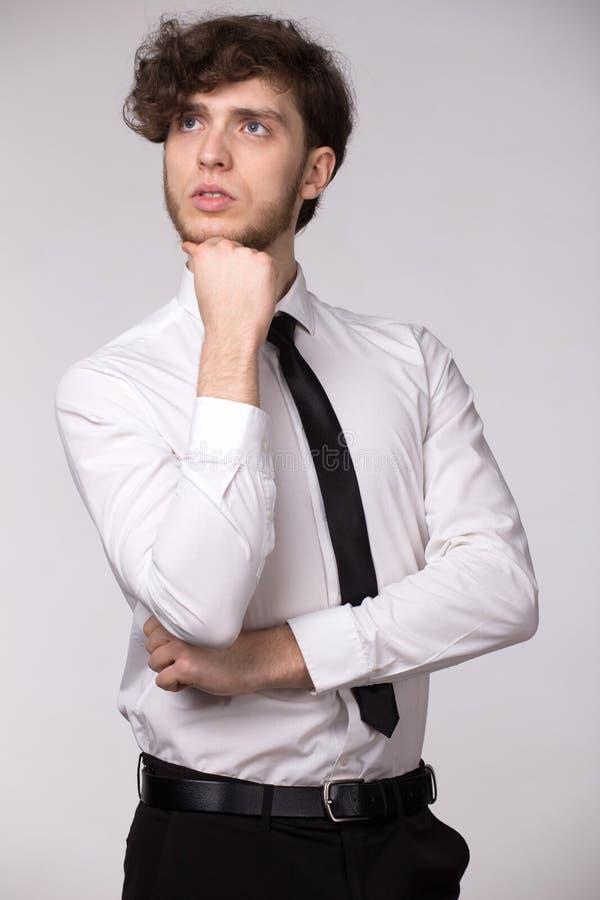 Retrato del hombre pensativo serio hermoso en la camisa blanca, mirando el pensamiento ascendente en el problema, sosteniéndose l foto de archivo