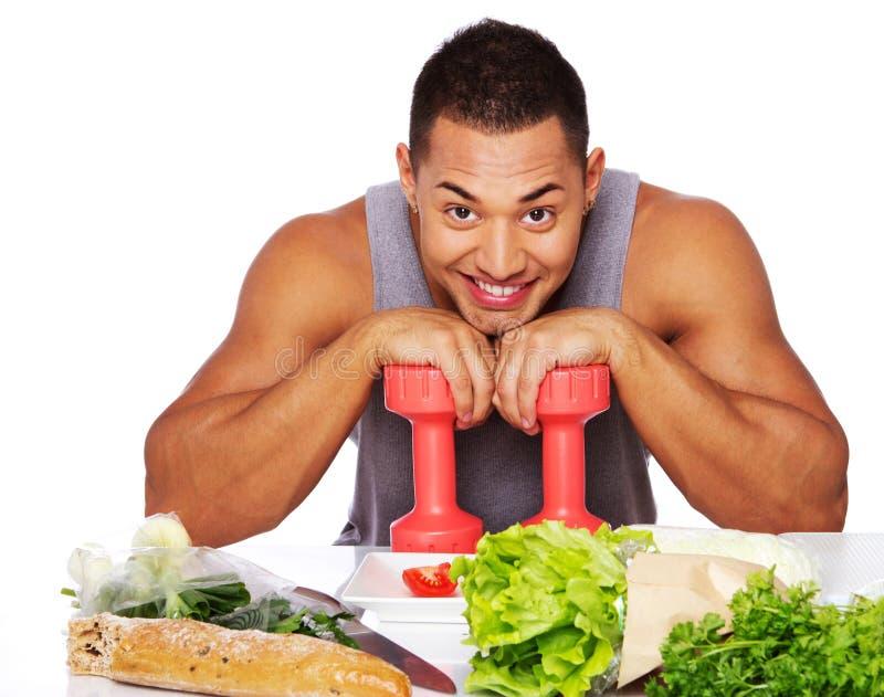 Retrato del hombre sano que presenta en estudio con pesas de gimnasia imagen de archivo libre de regalías