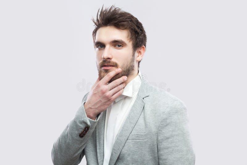 Retrato del hombre serio barbudo marrón hermoso en la camisa blanca y la situación gris casual del traje, tocando su cara y mirán imagen de archivo