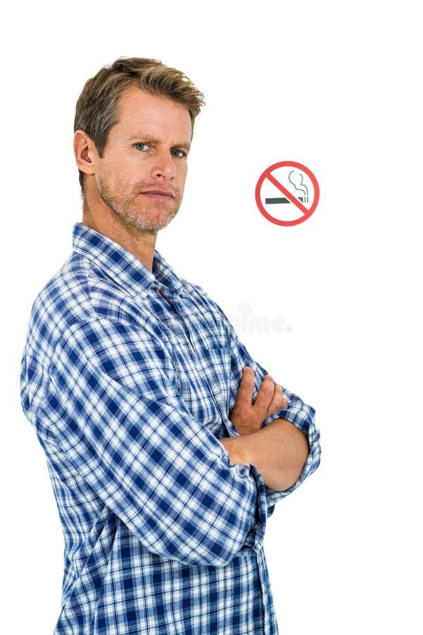Retrato del hombre serio con la muestra de no fumadores fotos de archivo