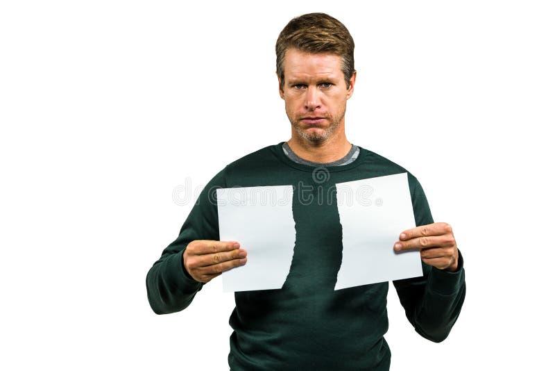 Retrato del hombre serio que lleva a cabo documentos rasgados foto de archivo libre de regalías