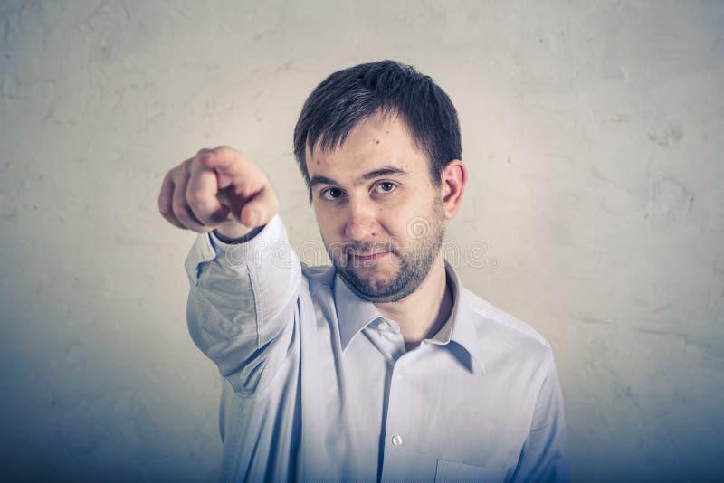 Retrato del hombre serio que señala el finger lejos en un fondo gris imágenes de archivo libres de regalías
