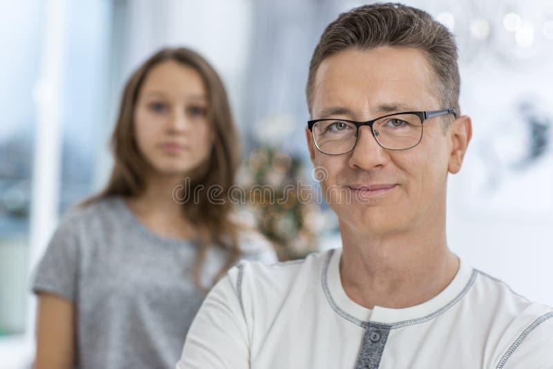 Retrato del hombre sonriente con la hija que se coloca en fondo en casa imagenes de archivo