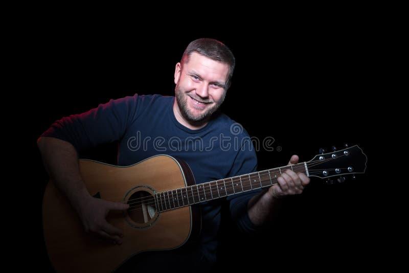 Retrato del hombre sonriente de A con la guitarra foto de archivo libre de regalías