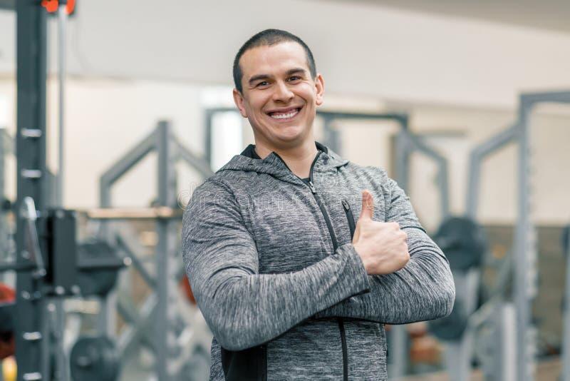 Retrato del hombre sonriente deportivo muscular que muestra los pulgares para arriba en el gimnasio, instructor hermoso que mira  fotos de archivo libres de regalías