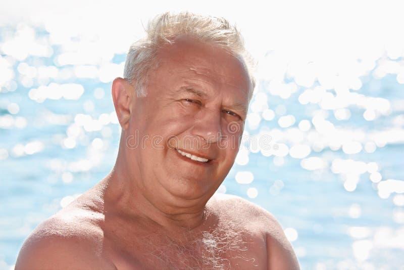 Retrato del hombre sonriente mayor en la costa fotos de archivo