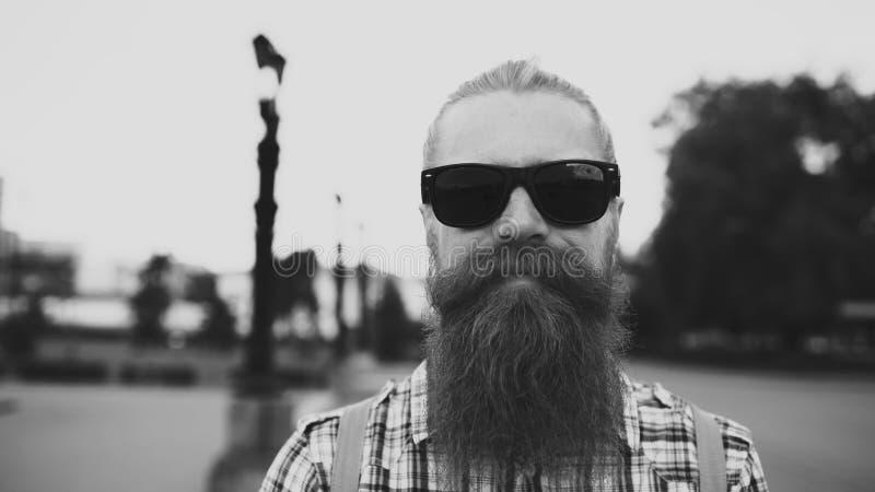 Retrato del hombre turístico barbudo del inconformista en las gafas de sol que miran la cámara y que sonríen en el fondo de la ci imágenes de archivo libres de regalías