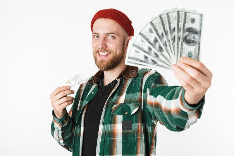 Retrato del hombre unshaved que sostiene la tarjeta de crédito y del fan del dinero del dólar, mientras que se coloca aislado sob foto de archivo
