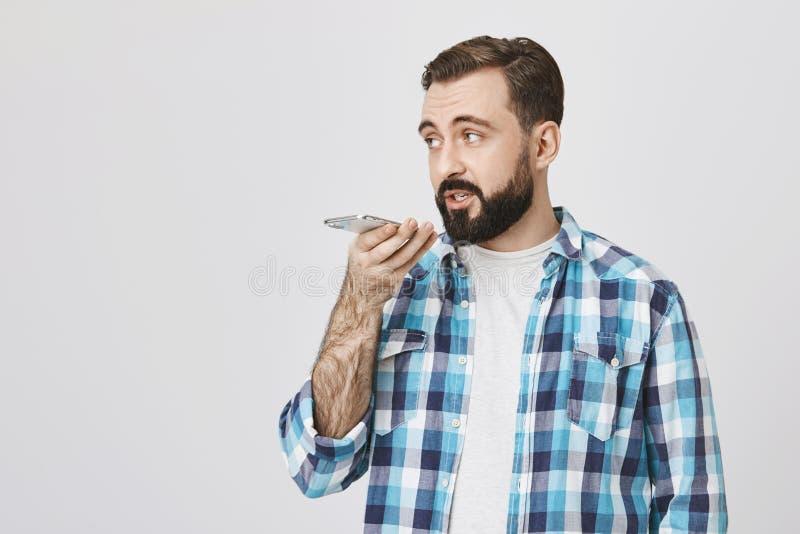 Retrato del inconformista adulto con la barba y del bigote que sostiene smartphone cerca de boca mientras que recodring masaje de imagen de archivo libre de regalías