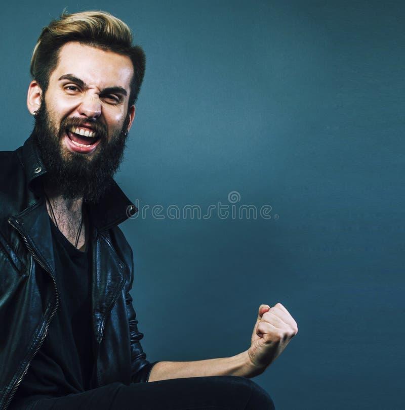 Retrato del individuo barbudo joven del inconformista que sonríe en fondo gris fotos de archivo