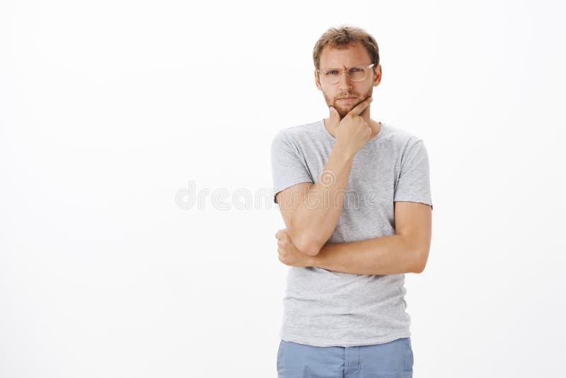 Retrato del individuo caucásico dudoso que bizquea la barbilla de frotamiento y de mirar fijamente centrado en la cámara mientras imagenes de archivo