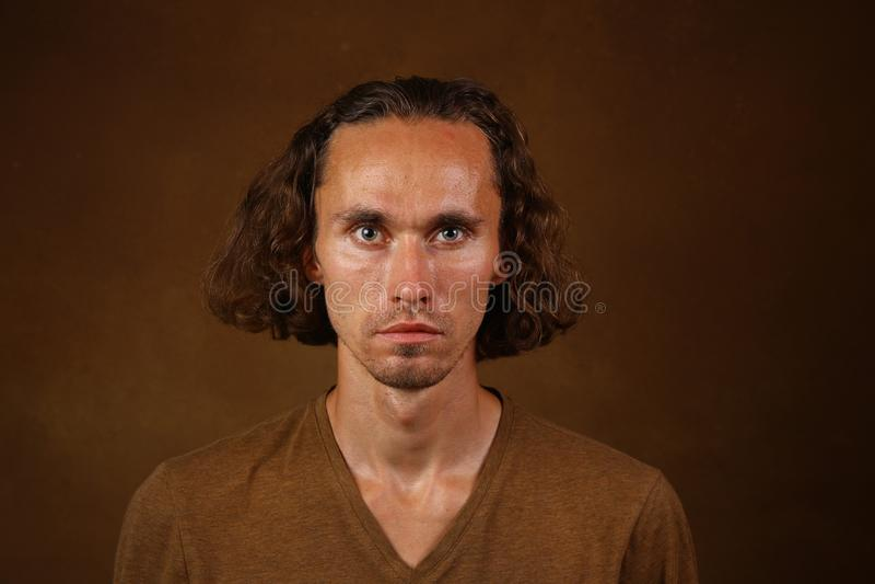 Retrato del individuo elegante con el pelo largo que lleva la camiseta marr?n que mira con sus ojos marrones la c?mara fotografía de archivo