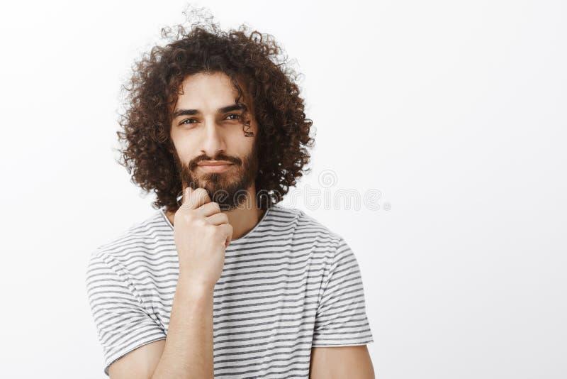 Retrato del individuo hispánico elegante y creativo hermoso con corte de pelo afro, celebrando la mano en barba y la mirada centr imagenes de archivo