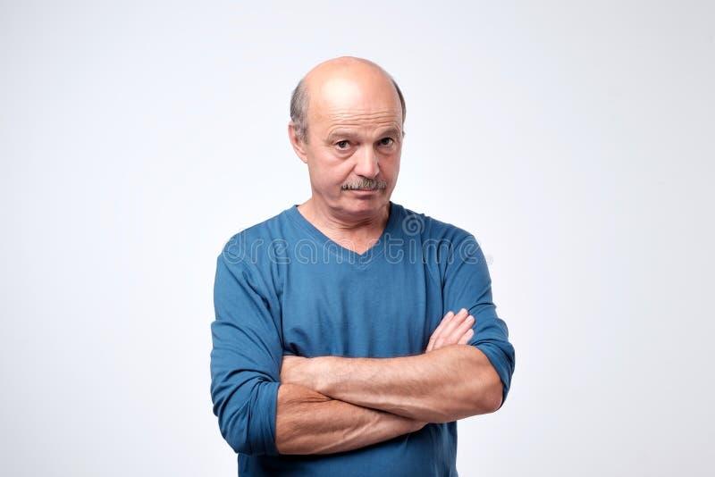 Retrato del individuo serio confiado maduro en camiseta azul fotos de archivo libres de regalías