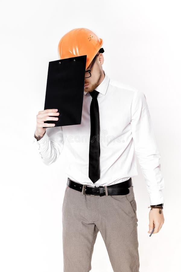 Retrato del ingeniero de construcción joven en casco anaranjado con la carpeta en el fondo blanco foto de archivo libre de regalías