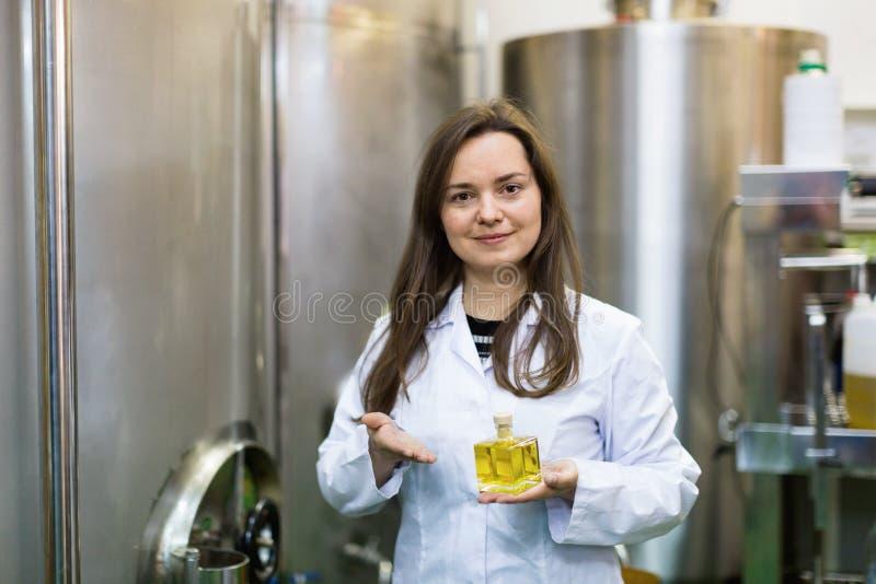 Retrato del ingeniero de sexo femenino sonriente que sostiene la botella de aceite del perfume fotografía de archivo