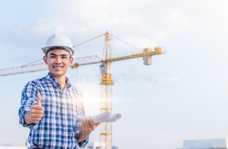 Retrato del ingeniero llevar un casco de seguridad blanco y sostener el modelo con el emplazamiento de la obra y el fondo de la g imagen de archivo libre de regalías