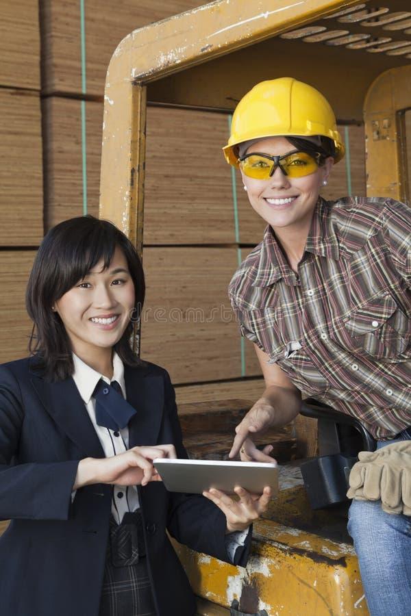 Retrato del inspector de sexo femenino y del trabajador industrial que usa la tableta imagen de archivo