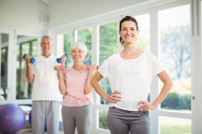 Retrato del instructor femenino que se coloca con los pares mayores mientras que ejercita con pesa de gimnasia foto de archivo