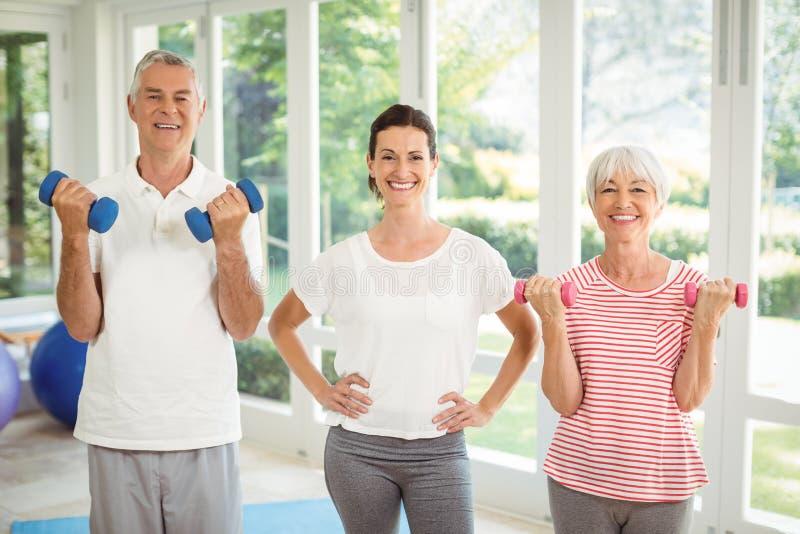 Retrato del instructor femenino que se coloca con los pares mayores mientras que ejercita con pesa de gimnasia fotos de archivo