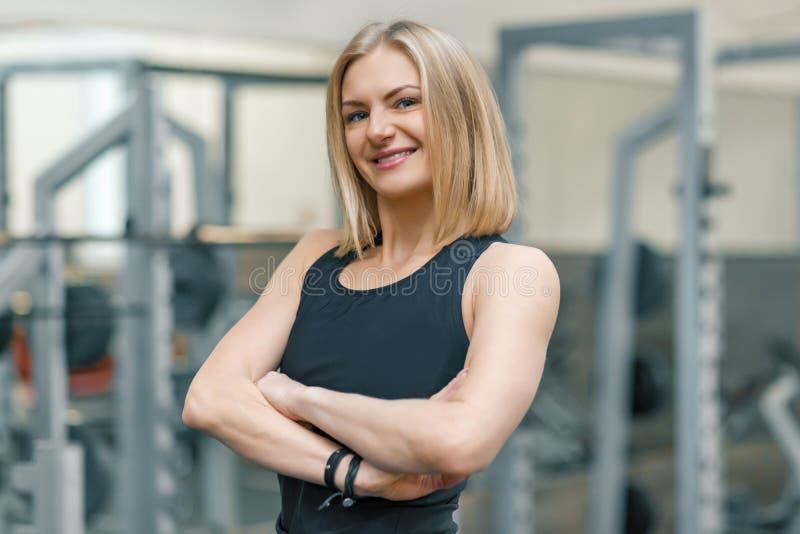 Retrato del instructor personal de la mujer rubia adulta de la aptitud con las manos dobladas en el gimnasio, hembra sonriente he fotografía de archivo libre de regalías