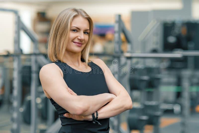 Retrato del instructor personal de la mujer rubia adulta de la aptitud con las manos dobladas en el gimnasio, mirada sonriente he imagen de archivo