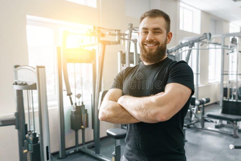 Retrato del instructor personal sonriente de la aptitud en el gimnasio, hombre confiado con las manos dobladas que miran la cámar foto de archivo libre de regalías