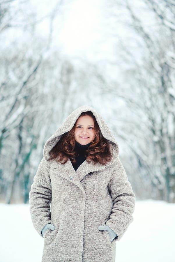 Retrato del invierno de la mujer atractiva joven Muchacha bonita que sonríe en parque del invierno Mujer feliz en capa que camina fotos de archivo libres de regalías