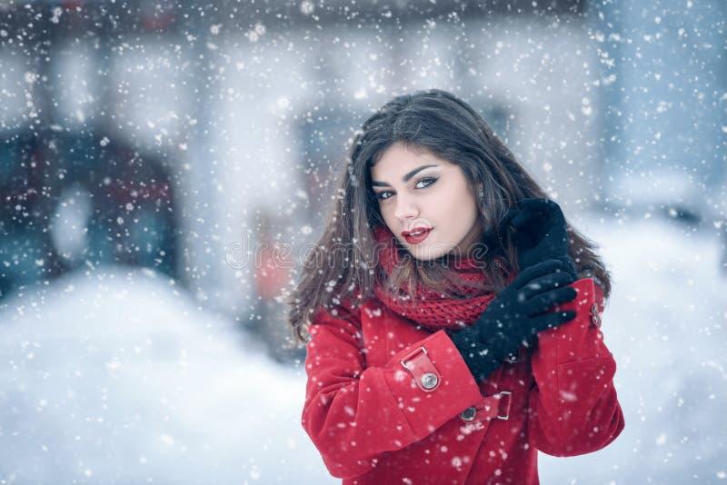Retrato del invierno de la mujer morena hermosa joven que lleva la redecilla hecha punto y la capa roja cubiertas en nieve Fashio imagen de archivo