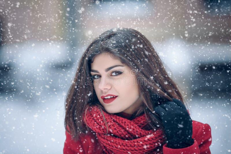 Retrato del invierno de la mujer morena hermosa joven que lleva la redecilla hecha punto y la capa roja cubiertas en nieve Fashio fotografía de archivo libre de regalías
